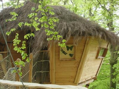 Entrée de la cabane champêtre avec sa belle avancée de toit qui permet de s'abriter. Sa toiture faite de brémaille ressemble à s'y méprendre à des brindilles très fines ce qui lui confère un aspect très naturel.