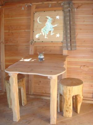 Le coin repas de cette cabane dans les arbres est composée d'une table et de tabourets taillées dans du bois brut.