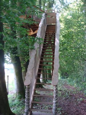La cabane de la ferme est la cabane dans les arbres la plus facile d'accès de notre site grâce à son escalier droit sécurisé par des filets. A conseiller aux personnes ayant le vertige, à mobilité réduite et aux enfants en bas âge. L'escalier permet d'arriver sur la terrasse attenante à la cabane.