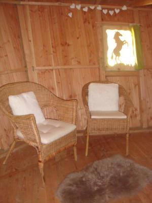 La cabane de la ferme offre un coin détente avec deux bons fauteuils pour ceux ou celles qui ont envie de profiter de l'intérieur de cette cabane dans les arbres.