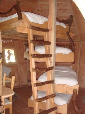 Les lits sont en suspension les uns au dessus des autres, en quinconce comme dans le principe d'un escalier en colimaçon. Le lit double est tout en haut, il est accessible par une échelle rigide. Les autres lits simples sont accessibles soit directement ou par une échelle souple. Cette configuration pour le moins originale permet d'avoir beaucoup d'espace dans cette cabane, d'où le coin détente crée avec des fauteuils.