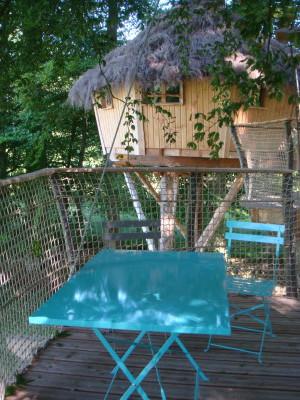 Le premier plan permet de voir la terrasse avec vue sur la cabane des sous bois